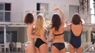Sexy women waving hand. Back view of hot girls in swimsuit waving good bye near pool. Enjoy summer fun. Four woman wave hands to someone. Summer holiday. Female pool party