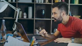 Shocked businessman looking at laptop in office. Joyful business man showing yes sign. Happy student reading good news on laptop computer in home. Young man win cash in online game