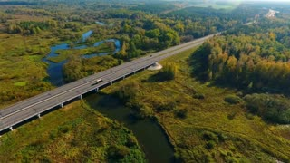 Sky view cars driving along bridge in nature. Car traffic on bridge over river. Aerial landscape of highway road above river. Highway road on river landscape. Cars moving on highway road landscape