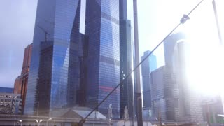 Skyscrapers of huge metropolis running past in window. Travel around city. Futuristic cityscape view with modern skyscrapers behind window