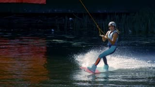 Slim girl waterskiing during her vacations. Extreme water sports. Healthy lifestyle concept. Girl riding on wakeboarding. Woman training stunt on wakeboard on water before competition. Water boarding
