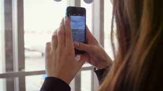 Smartphone video of plane taking off. Woman taking mobile video of plane take off. Tourist photographer taking pictures on smartphone camera. Woman use mobile for video at airport