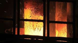 Smelting furnace sparks. Hot steel sparks from industrial furnace. Molten metal sparks in blast furnace. Sparks fire furnace