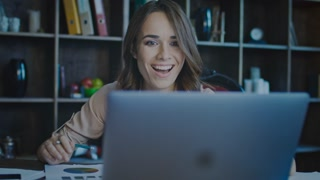 Smiling businesswoman looking at laptop screen in office. Happy business woman enjoy good news. Good business achievement. Satisfied woman clapping hands in dark cozy office. Female manager enjoy work