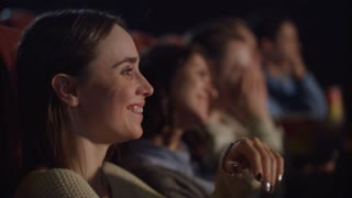Smiling girl watching theater performance and laughing. Spectators have fun. Cinema people watching comedy movie. Close up of woman face watching funny movie at cinema in slow motion