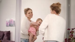 Smiling woman dancing with baby on hands. Happy mother with child looking mirror. Enjoy motherhood. Joyful mom with infant dance at home. Sweet baby love. Beautiful family enjoyment