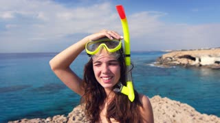 Smiling woman in diving mask on sea background. Portrait of smiling girl going to dive on stony beach. Joyful woman in snorkel on head near sea. Summer diving on Cyprus beach