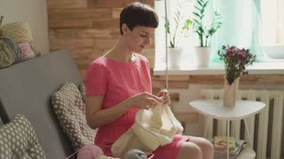 Smiling woman knitting woolen yarn sitting on couch in room. Woman hobby