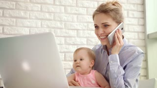 Smiling woman with child speaking phone. Happy mother with baby talking on phone and looking laptop. Happy business mother working at home. Cheerful mom with baby working on laptop. Enjoy motherhood