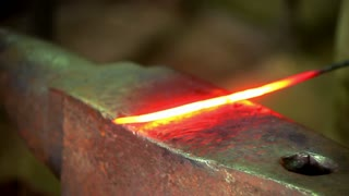 Smith beating hammer hot iron on anvil in forge. Blacksmith forging red hot metal on anvil. Close up red hot metal on blacksmith anvil. Metal forging. Hot iron on anvil blacksmith