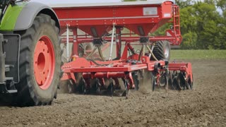 Sowing machine plowing and sowing seeds in soil on rural field. Process sowing plowed land. Farming machinery working on agricultural field. Farming industry. Arable farming