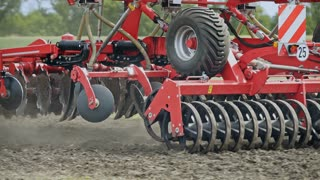 Sowing machine working on farming field. Agricultural tractor with trailer seeder sowing plowed land. Farming equipment for field sowing. Agricultural technology. Seed drill. Agricultural machinery