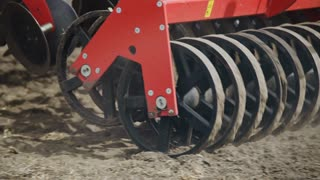 Sowing machine working on farming field. Close up soil sowing process. Agricultural equipment for field sowing. Farming machinery. Agricultural technology. Agriculture machinery parts