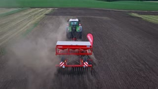 Sowing machine working on plowed field. Aerial view sowing machine on agricultural field. Agricultural industry. Farming equipment for field sowing. Agriculture machinery. Agriculture industry