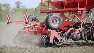 Sowing machine working on plowed field. Sowing machine on agricultural field. Farming equipment for field sowing. Agricultural machinery. Agricultural technology