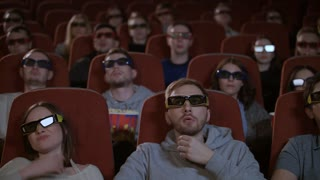 Spectators in 3d glasses watching film in cinema. People watching film at movie theatre. 3d movie audience. People in 3d glasses at movie hall in slow motion