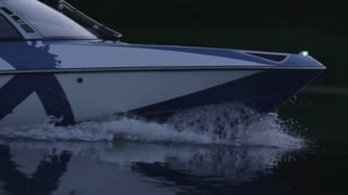 Speedy motor boat floating on river in evening. Close up of boat bow moving on water. Cruising on luxury yacht. Boating on lake. Fast moving modern powerboat