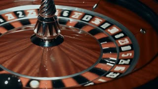 Spinning roulette wheel with stopped ball. Close up classic casino roulette with black and red sectors. Traditional game of chance in casino concept. Gambling table with rotating wheel of fortune