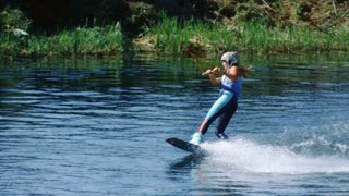 Sport woman on board sliding on water. Girl studying wakeboarding on lake. Water boarder wakeboarding on river in slow motion. Active people. Woman water skiing lake. Extreme lifestyle