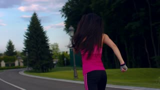 Sport woman running in city park. Woman running in slow motion. Running woman on park road. Outdoor fitness workout. Fitness training at morning. Back view of female runner with long hair