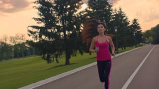 Sport woman running on park road. Asian woman running park. Fit woman running in slow motion. Morning training workout. Young woman fitness workout outdoor. Fit girl jogging outside