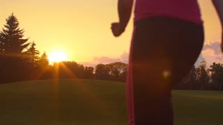 Sport woman running outdoor at sunset. Young woman running in park at evening. Back view of running woman on meadow at sunset. Sporty girl run away from camera. Fitness training outdoor