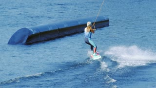 Sports woman training wake boarding tricks in cable wake park. People enjoys riding wakeboard on lake. Young woman water skiing on pipe. Active girl training wake boarding stunt on lake