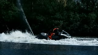 Sportsman swirling on speedy jet ski on river. Extreme water sport concept. Rider drive jet ski in slow motion. Male extreme jet skiing