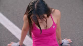 Sporty woman rest after fitness exercise. Close up of tired asian woman sitting on road. Tired woman after hard training. Sexy woman touches her hair. Exhausted female runner sitting on asphalt road