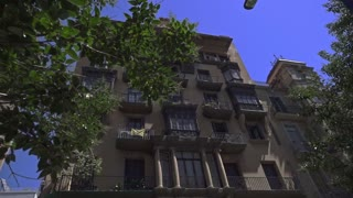 Steadicam shot of house with balconies in Barcelona's Gothic Quarter. Facades old houses in streets of Barcelona. Old spanish building exterior