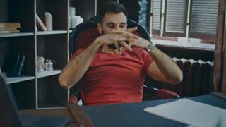 Successful businessman relaxing in cozy office. Portrait of young entrepreneur enjoying his new office. Bearded man relaxing on chair with hands behind head in work place