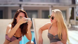 Summer girls in sunglasses taking selfie at chaise longue. Happy women sunbathing and take selfie at swimming pool. Girls friends taking photo on mobile phone at resort. Female fun relax