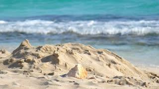 Summer sand beach with ocean waves. Sand heap on beach. Sea sand landscape. Tropical beach landscape. Summer vacation landscape