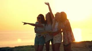 Summer women waving hands at sunset. Happy girls looking for someone at beach sunset. Female vacation travel. Enjoy summertime. Joyful woman call someone far away. Cheerful women flirting on beach