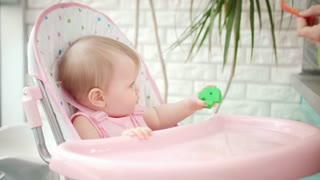 Sweet baby girl eating vegetable. Close up of mother hand feeding child with red pepper. Baby healthy food. Toddler in chair tasting new meal. Little kid eat vegetables. Child have dinner