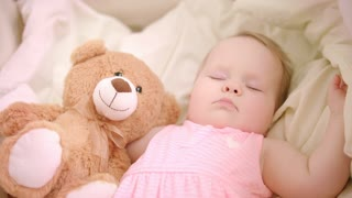Sweet baby girl sleeping with toy in crib. Close up of infant sleeping in cot. Beautiful toddler sleeping with toy bear. Sweet bedtime. Little girl dream in bed. Adorable childhood. Tired baby relax
