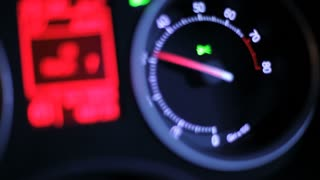 Tachometer arrow. Car dashboard at night. Car rpm. Driving fast at night. Rotation of arrow on tachometer. Close up of dashboard auto illuminate. Tachometer speed. Red lights on car control panel