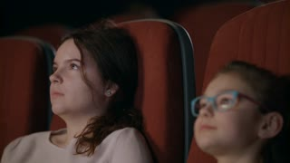 Teenage girl watching movie in cinema with younger sister. Young girls watching movie in cinema. Teenager receiving text message during watching movie