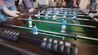 Teenagers playing table football. Young office people enjoying table soccer game. Close up of table football kicker game
