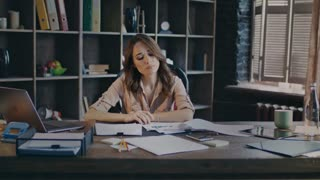 Thinking businesswoman sitting at desk. Sad business woman reading graphs on documents. Paperwork in office at evening. Female marketer thinking decision about business problem solution
