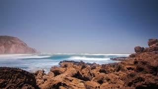 Time lapse of beautiful ocean waves splashing rocky shore. Ocean tide on rocky beach. Ocean waves splash on rocky shore. Landscape ocean shore. Water tide on rock shore