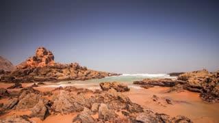 Time lapse of morning tide sea on rocky beach background. Sea wave splash on rocky beach. Landscape sea tide on rocky beach. Timelapse of ocean waves crashing on rocks