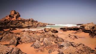 Timelapse of waves splashing on rocky coast. Beautiful sea waves crashing on rocks. Landscape sea tide on rocky beach. Sea waves crashing on beach rock