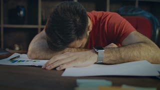 Tired business man lying on papers at table. Close up of businessman sleeping on desk. Overworked man sleep on documents on desk. Exhausted employee lying at workplace