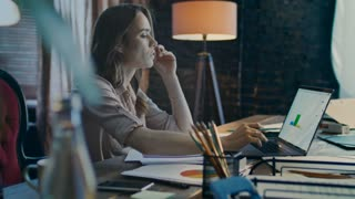 Tired business woman working on laptop with data graphics in dark office. Business process work. Thoughtful businesswoman analyzing market statistic at evening. Female marketer looking market graph