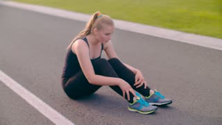Tired runner sitting on asphalt road. Exhausted female runner breathing hard after running marathon. Exhausted woman recovering after running exercise at summer. Breathing woman athlete after training