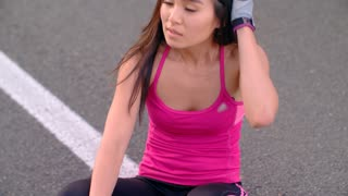 TIred woman after jogging. Close up of asian woman after hard training. Sensual woman resting after outdoor fitness workout. Sexy woman sitting on road. Exhausted female runner after running marathon