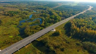 Top view car bridge over river. Cars moving along bridge at nature. Highway road above river at field. Highway road on river landscape. Aerial landscape of cars driving on highway road at nature