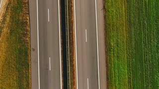 Top view car moving along highway in green field. Aerial landscape car ride on country road. Cars driving on suburban road. Highway road in green meadows. Car traffic highway landscape