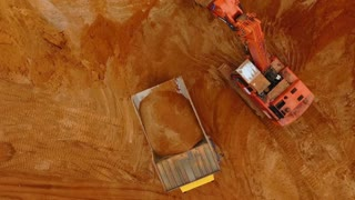 Top view of excavator pouring sand in dump truck. Aerial view of mining sand process at sand quarry. View from above of mining machinery. Mining industry. Mining equipment working at sand mine
